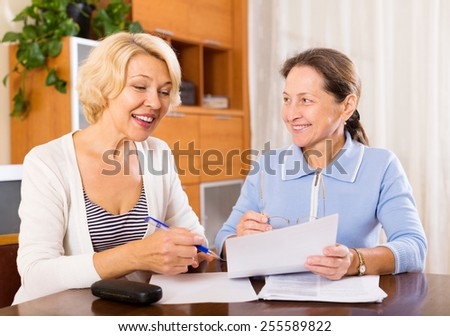 Smiling senior ladies signing documents at home.Focus on the woman on the left - stock photo
