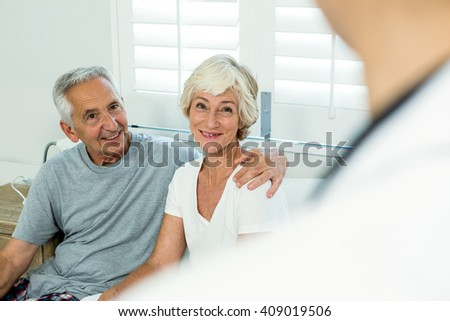Smiling senior man and woman with doctor at home - stock photo