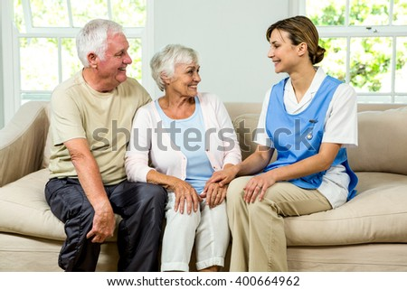 Smiling senior man and woman with nurse on sofa at home - stock photo