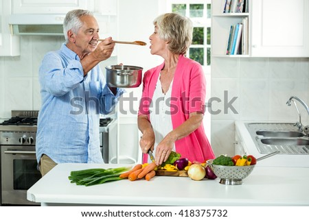 Smiling senior man feeding food to woman while standing in kitchen - stock photo