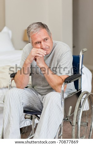 Smiling senior man in his wheelchair  at home - stock photo