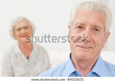 Smiling senior man smiling with his old wife in background - stock photo
