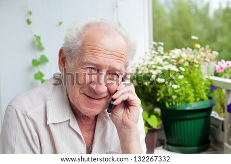 smiling senior man speaking on the phone with somebody - stock photo