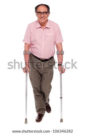 Smiling senior man walking with two crutches. All on white background - stock photo