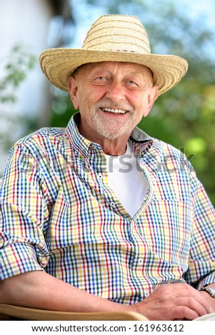 Smiling senior man with a straw hat outdoors