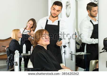 Smiling senior mature woman at the hairdresserâ??s chair  - stock photo
