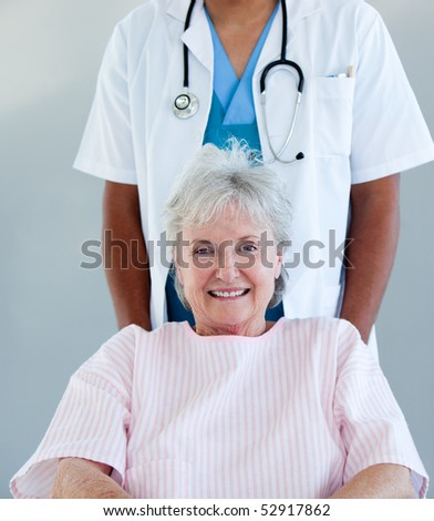 Smiling senior patient sitting on a wheelchair in a hospital - stock photo