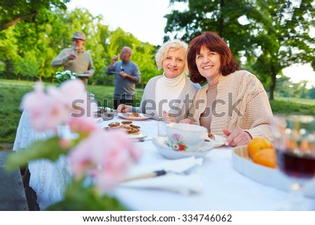 Smiling senior people celebrating birthday party in a summer garden - stock photo