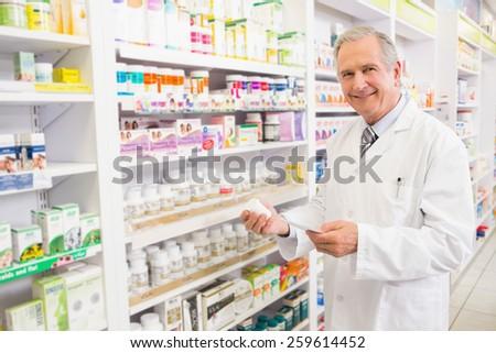 Smiling senior pharmacist holding medicine and prescription in the pharmacy - stock photo