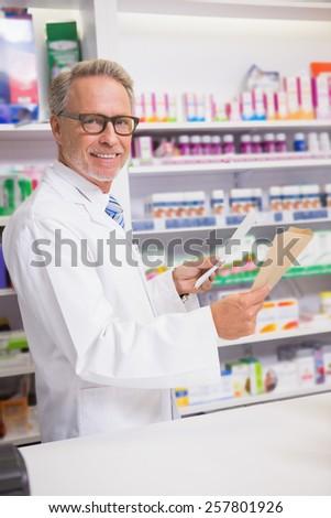 Smiling senior pharmacist holding prescription in the pharmacy - stock photo