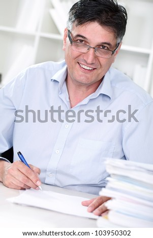 Smiling senior professor review tests in his office - stock photo