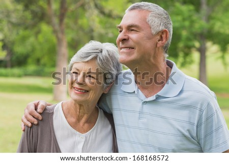 Smiling senior woman and man with arms around at the park - stock photo