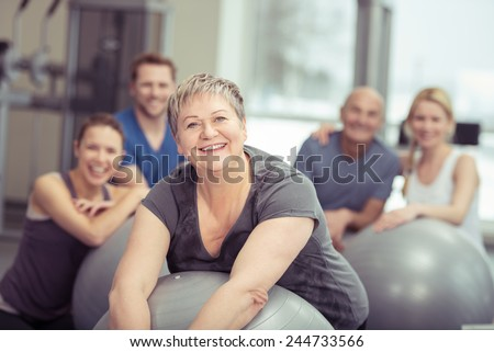 Smiling senior woman enjoying pilates class at the gym posing leaning on her ball smiling at the camera with the class behind - stock photo