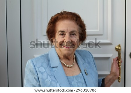 Smiling senior woman exiting her house pausing with her hand on the latch of the door to smile at the camera - stock photo