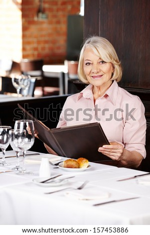 Smiling senior woman in a restaurant looking at the menu