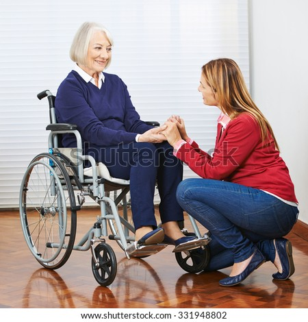 Smiling senior woman in wheelchair with adult daughter holding hands