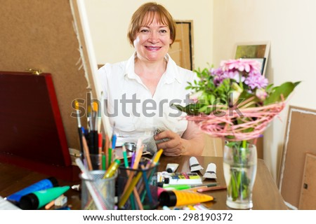 Smiling senior woman painting a new picture - stock photo