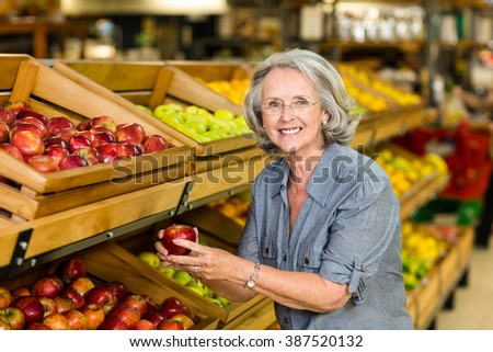 Smiling senior woman picking apple at the grocery shop