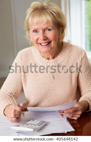 Smiling Senior Woman Reviewing Domestic Finances - stock photo