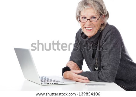 Smiling senior woman sitting at a white table in her glasses using a laptop computer on white - stock photo