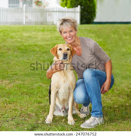 Smiling senior woman sitting with her dog in the garden
