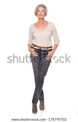 Smiling senior woman standing in studio in front of white background - stock photo