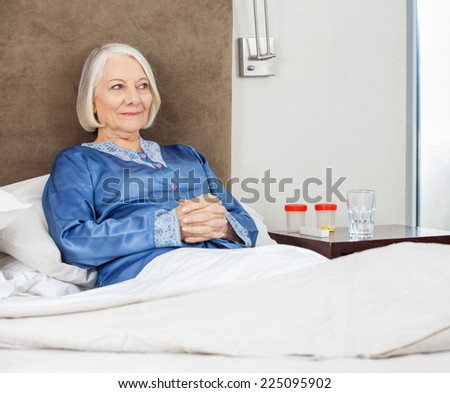 Smiling senior woman with hands clasped relaxing on bed at nursing home - stock photo