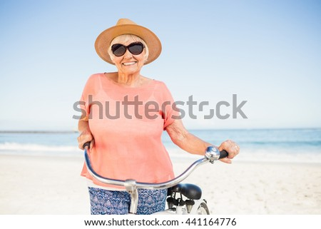 Smiling senior woman with her bike on the beach - stock photo