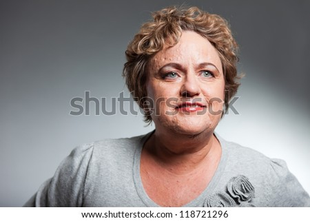 Smiling senior woman with short curly hair. Studio shot against grey. - stock photo