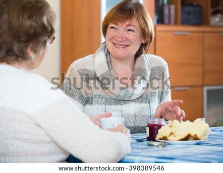 Smiling senior women having nice conversation while tea drinking - stock photo