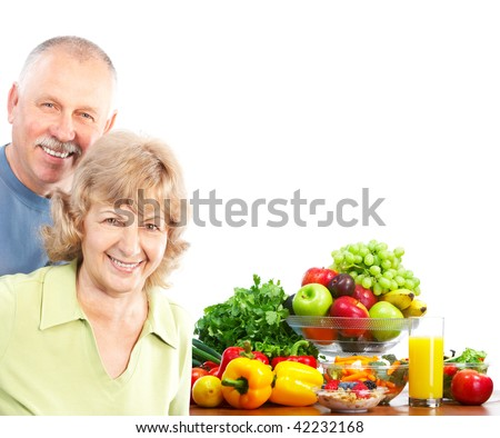 smiling seniors couple with fruits and vegetables. Over white background
