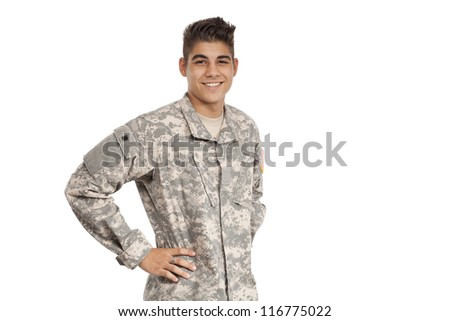 Smiling serviceman standing with hands on hips - stock photo
