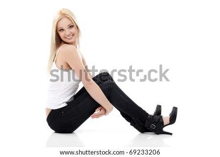 Smiling sexy blond woman in white shirt and  jeans sitting on a floor isolated on white - stock photo