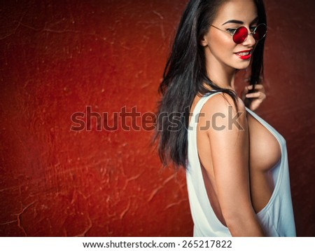 Smiling sexy girl on red background - stock photo