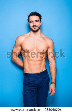 smiling shirtless man with beard on blue background - stock photo