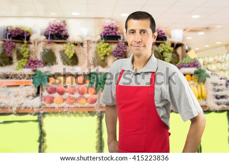 smiling shopman at the greengrocer with copyspace - stock photo