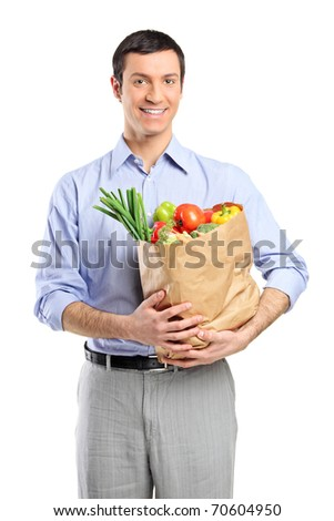 Smiling shopping man holding bag filled with fruits, food, vegetables from supermarket isolated on white background - stock photo