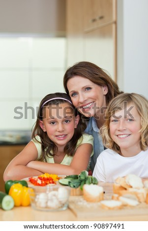 Smiling siblings and mother making sandwiches together