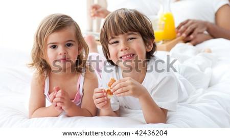 Smiling siblings having breakfast lying on the bed - stock photo