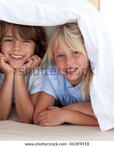 Smiling siblings playing under covers in the bedroom - stock photo
