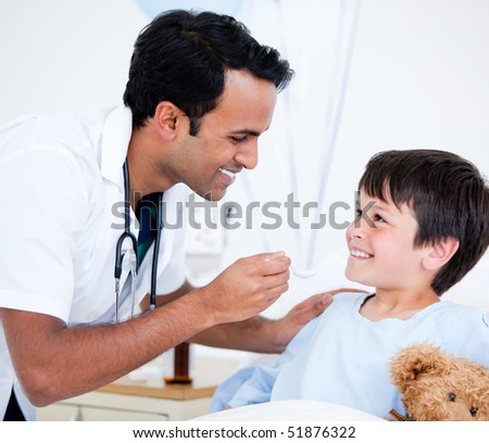 Smiling sick little boy taking medicine sitting on a hospital bed - stock photo