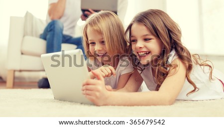 smiling sister with tablet pc and parents on back - stock photo