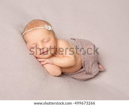 smiling sleeping newborn girl with hands under her head covered with knitted shawl