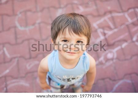 smiling small boy looking up at camera - stock photo