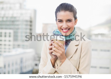 Smiling smart brown haired businesswoman holding a cup of coffee outdoors - stock photo