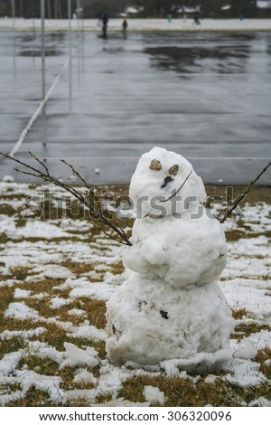 Smiling snowman in park with rock eyes and stick arms.