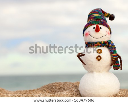 Smiling snowman on the sea beach. Holiday concept can be used for New Year and Christmas Cards - stock photo