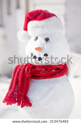 Smiling snowman with red santa hat and scarf