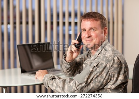 Smiling soldier talking on cellphone