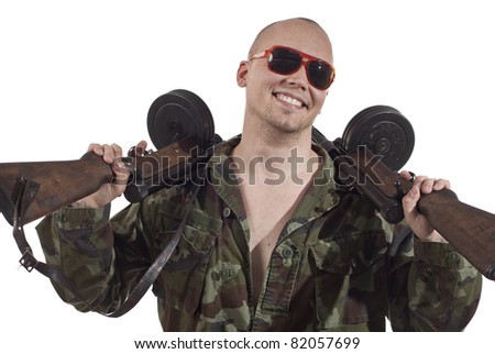 Smiling soldier with sunglasses and two machine guns. - stock photo